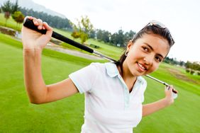 Girl playing golf and holding a golf-club at the field